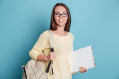 Beautiful young girl with bagpack and notebook over blue background Stock Photo