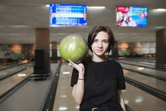 Beautiful young girl with a ball in her hands playing bowling and looking into the camera. Playing bowling club. Beautiful young girl with a ball in her hands royalty free stock image