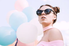 Beautiful and young girl with balloons in glasses. Bright portrait of beautiful girl with balloons Royalty Free Stock Photo