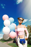Beautiful and young girl with balloons in glasses. Portrait of beautiful girl with balloons in park Royalty Free Stock Photo