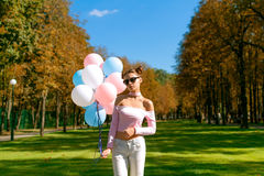 Beautiful and young girl with balloons in glasses. Portrait of beautiful girl with balloons in park Royalty Free Stock Photography