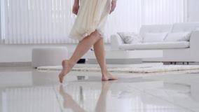 Beautiful young girl bare feet moving on interior in the living room in slow motion. View of young girl elegantly to. Walk. legs. Floor. Gait. Slow motion stock video footage