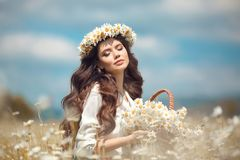 Beautiful young girl with basket of flowers over chamomile field. Carefree happy brunette woman with healthy wavy hair having fun. Outdoor in nature royalty free stock images