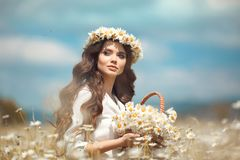 Beautiful young girl with basket of flowers over chamomile field. Carefree happy brunette woman with healthy wavy hair having fun. Outdoor in nature stock image