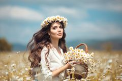 Beautiful young girl with basket of flowers over chamomile field. Carefree happy brunette woman with healthy wavy hair having fun. Outdoor in nature stock images