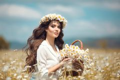 Beautiful young girl with basket of flowers over chamomile field. Carefree happy brunette woman with healthy wavy hair having fun. Outdoor in nature stock photos