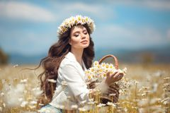 Beautiful young girl with basket of flowers over chamomile field. Carefree happy brunette woman with healthy wavy hair having fun. Outdoor in nature royalty free stock image