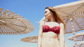 Beautiful young girl in a bathing suit stands on the beach umbrellas and looks away stock video footage