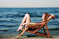 Beautiful young girl at the beach. Beautiful model is watching the see Royalty Free Stock Photo
