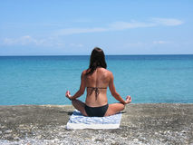 Beautiful young girl on the beach practicing yoga Royalty Free Stock Images