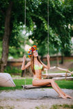 Beautiful young girl with beautiful smile on a swing on summer day outdoors Stock Photo