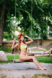 Beautiful young girl with beautiful smile on a swing on summer day outdoors Royalty Free Stock Photos