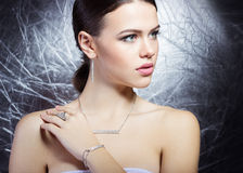 Beautiful young girl with beautiful stylish expensive jewelry, necklace, earrings, bracelet, ring, filming in the Studio Stock Images