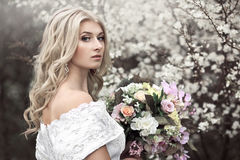 Beautiful young girl in a beautiful white dress with a bouquet near a flowering tree.
