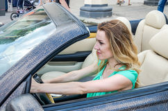 Beautiful young girl behind the wheel rides leather car cabriolet Stock Photos