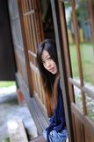 Beautiful young girl behind the wooden door Stock Image