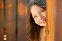 Beautiful young girl behind the wooden door royalty free stock photo