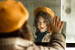 Beautiful young girl in beige hat looking at herself in the mirror stock photo