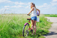 Beautiful young girl with bike in summer field Royalty Free Stock Photo