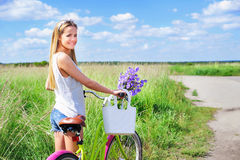 Beautiful young girl with bike in summer field Royalty Free Stock Photos