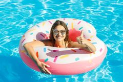 Beautiful young girl in bikini with donut inflatable pink circle in blue swimming pool stock image