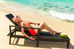 Beautiful young girl in bikini is lying on a sun lounger coast o Royalty Free Stock Images