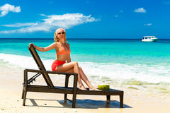 A beautiful young girl in bikini is sitting on a sun lounger coa Royalty Free Stock Photos