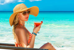 Beautiful young girl in bikini is sitting on a sun lounger coast Royalty Free Stock Photo