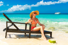 Beautiful young girl in bikini is sitting on a sun lounger coast Royalty Free Stock Images