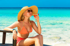 Beautiful young girl in bikini is sitting on a sun lounger coast Royalty Free Stock Images