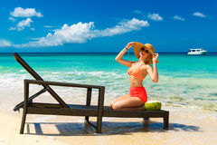 Beautiful young girl in bikini is sitting on a sun lounger coast Stock Image
