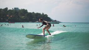 Beautiful young girl in bikini surfing. Tourism and recreation in Thailand. Charming cute Asian woman travel around the