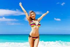 Beautiful young girl in bikini on a tropical beach. Blue sea in Royalty Free Stock Photo