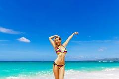 Beautiful young girl in bikini on a tropical beach. Blue sea in Royalty Free Stock Photography