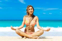 Beautiful young girl in bikini on a tropical beach. Blue sea in Stock Photo