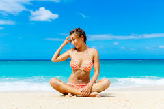 Beautiful young girl in bikini on a tropical beach. Blue sea in Stock Images