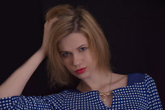 Beautiful young girl on a black background. In blue dress and red lips royalty free stock photography