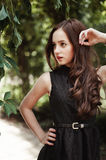 Beautiful young girl in black dress with long hair, super cute a Royalty Free Stock Image