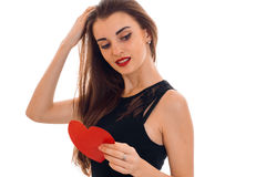 Beautiful young girl in a black dress looking down raised one arm to the hair and keeps a postcard sweetheart Stock Image