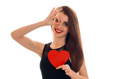 Beautiful young girl in a black dress and red lipstick on lips holding a card in the shape of a heart and second hand Royalty Free Stock Photography