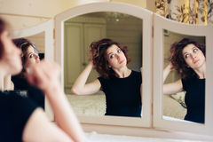 Beautiful young girl in a black dress sits in front of a vintage mirror, reflected in three mirrors Stock Image