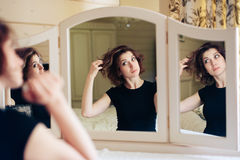Beautiful young girl in a black dress sits in front of a vintage mirror, reflected in three mirrors Royalty Free Stock Image