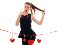 Beautiful young girl in a black dress stands near the tape with cards in the shape of hearts and surprise keeps hand Stock Image