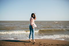 Beautiful young girl with black hair in a shirt and jeans has fun on the beach of the Azov Sea Stock Photography