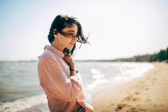 Beautiful young girl with black hair in a shirt and jeans has fun on the beach of the Azov Sea Royalty Free Stock Image