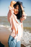 Beautiful young girl with black hair in a shirt and jeans has fun on the beach of the Azov Sea Royalty Free Stock Photography