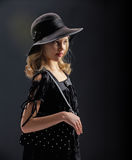 Beautiful young girl in a black hat. Royalty Free Stock Images