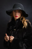 The beautiful young girl in a black hat with wide fields and  fur coat Stock Photography