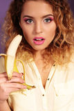 Beautiful young girl with blond hair and bright makeup with banana Royalty Free Stock Photo