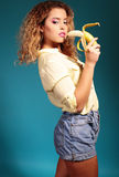 Beautiful young girl with blond hair and bright makeup with banana Royalty Free Stock Photography